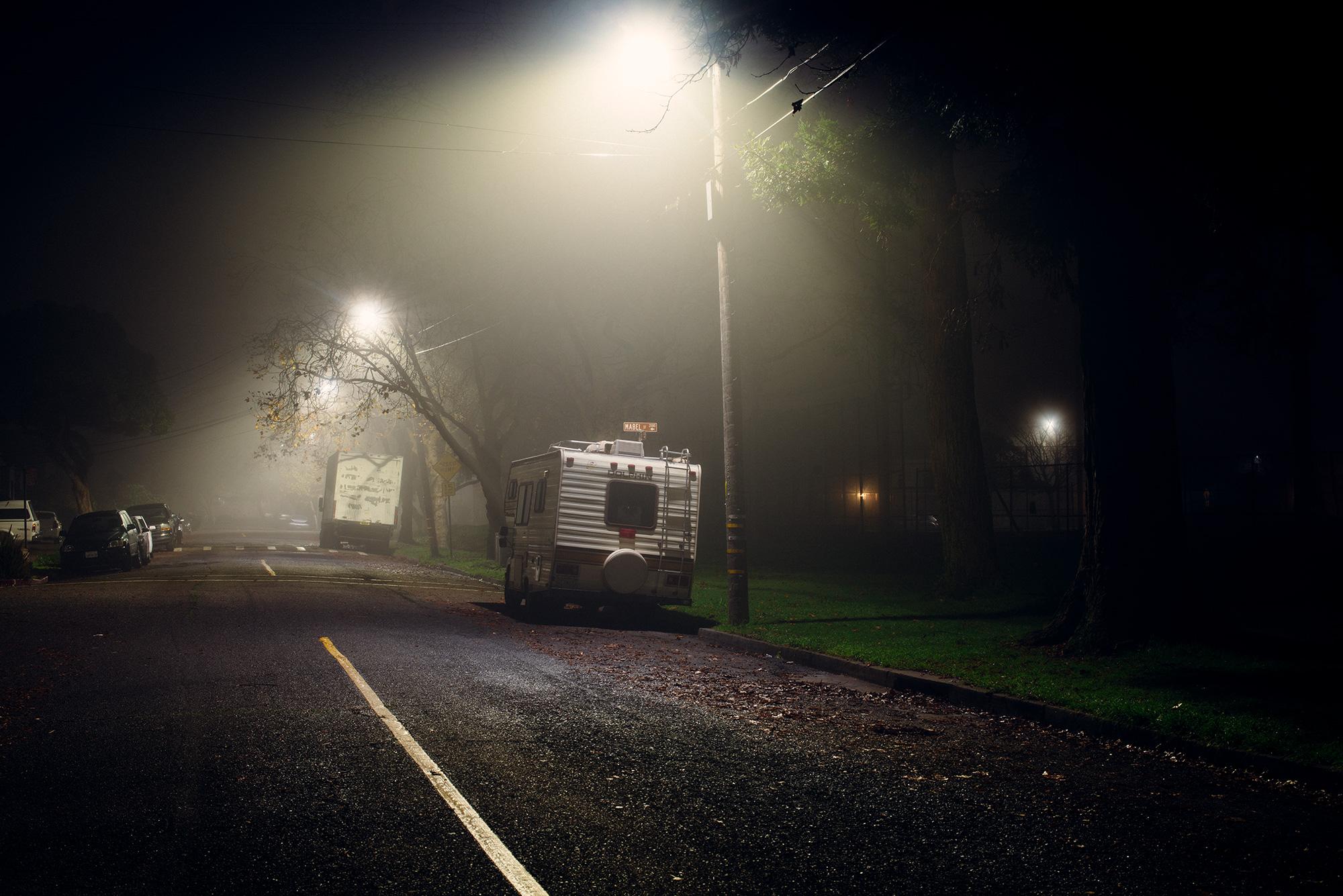 Van on street at night with street lights.