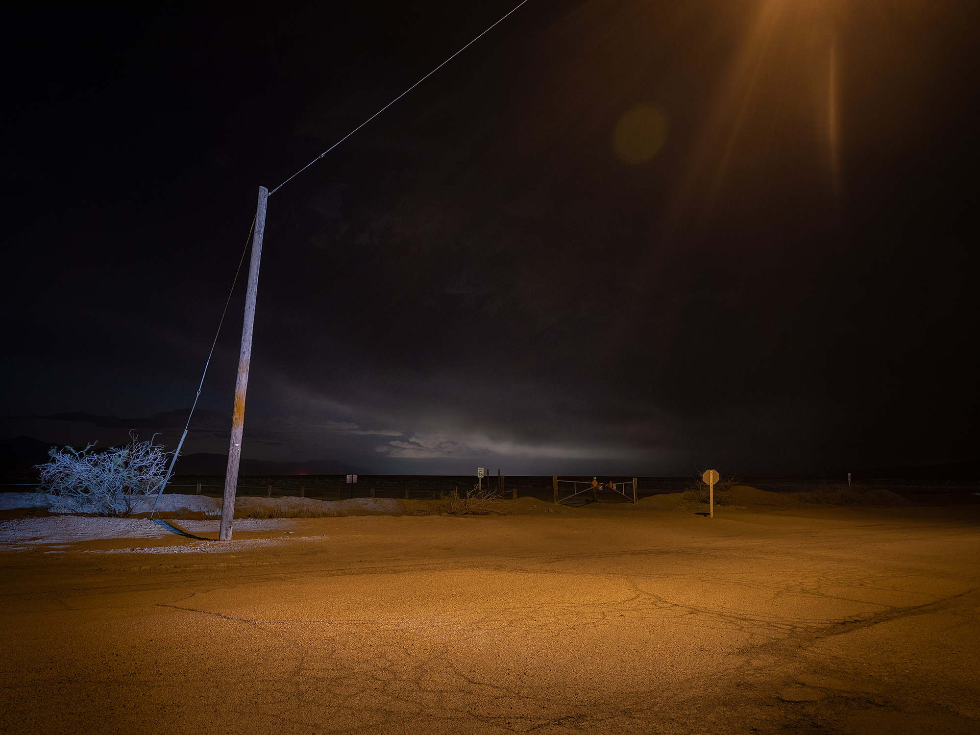 Landscape at night with sand storm in background.