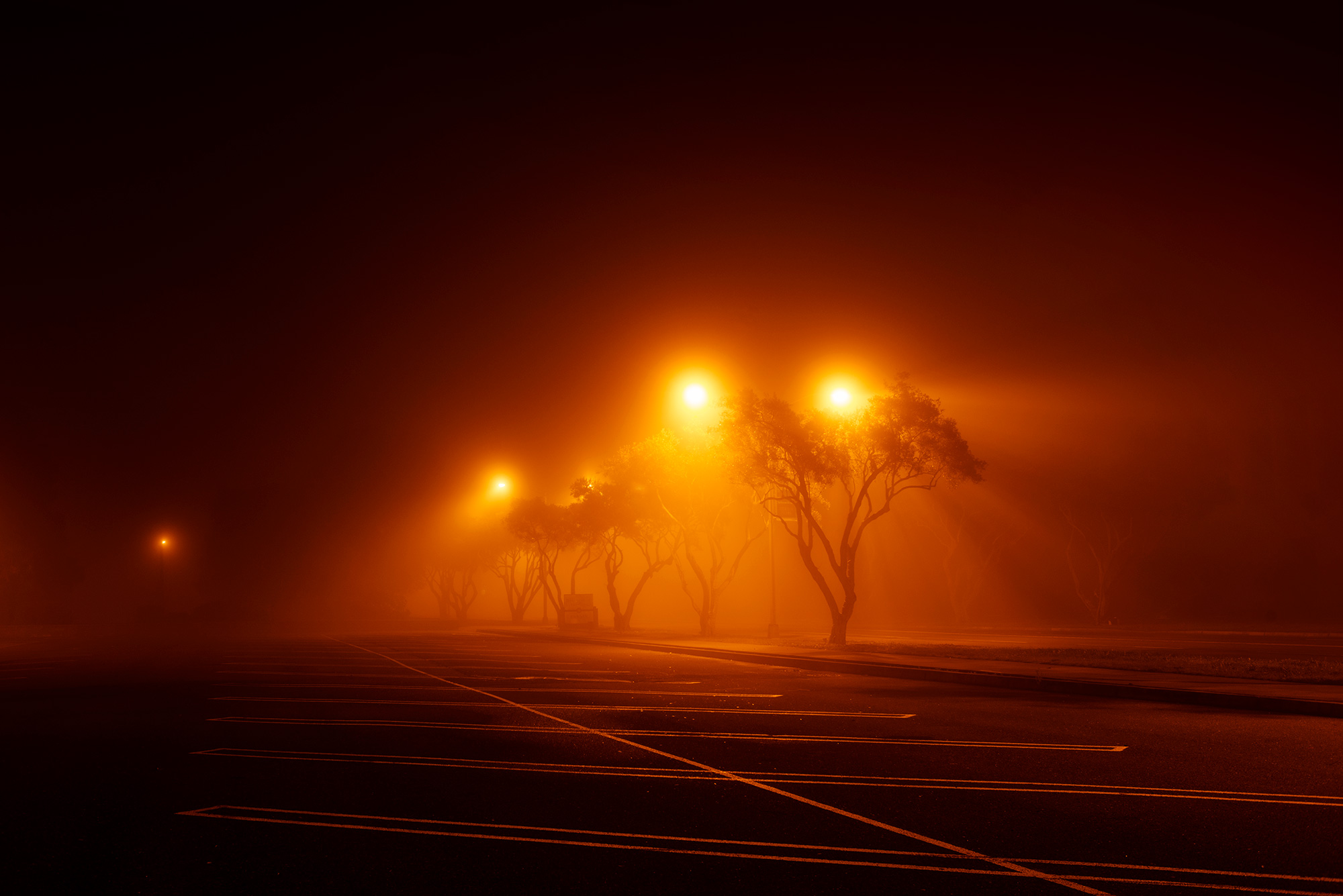 Parking lot at night with lights and fog.