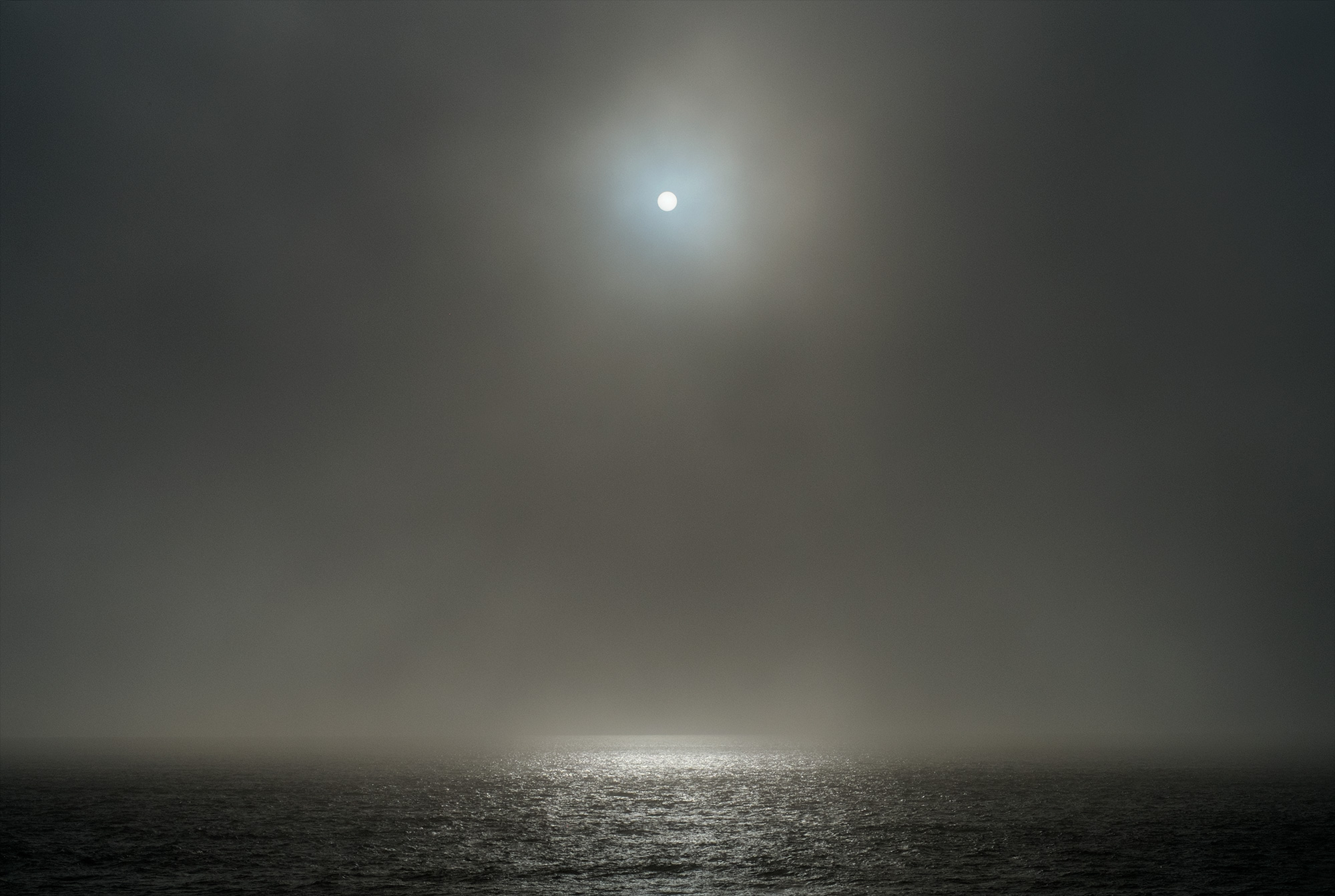 Sunrise over the pacific ocean with sun that looks like the moon.