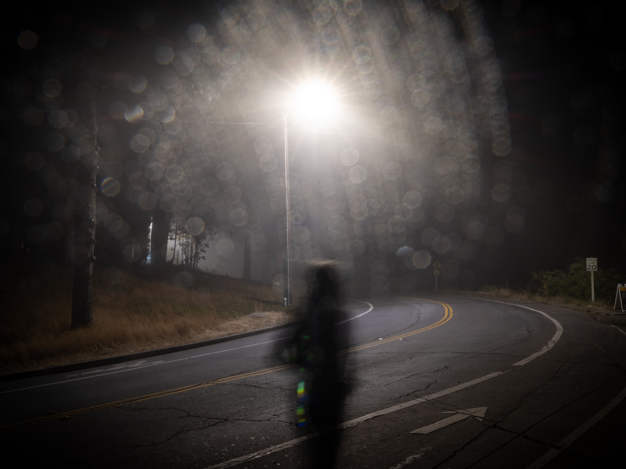 Person walking on roadway at night.