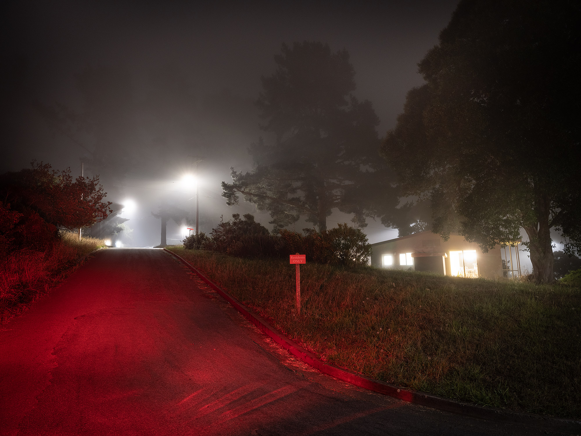 Image of military housing at night with red lights and fog.