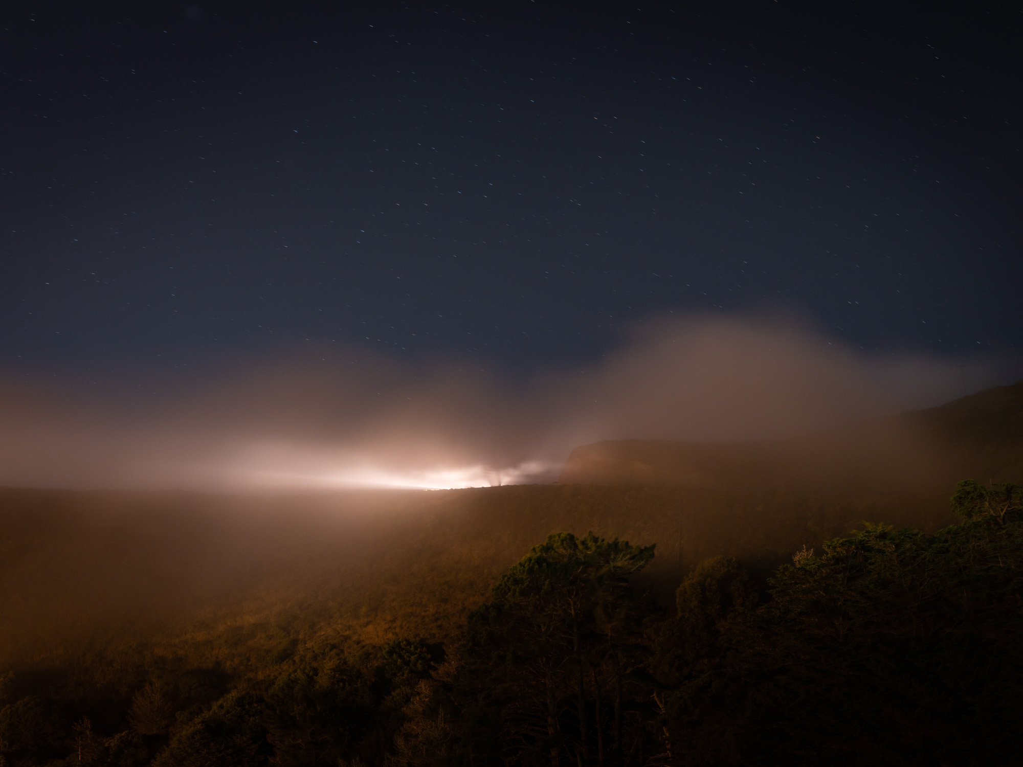 Light on hill at night overlooking trees.
