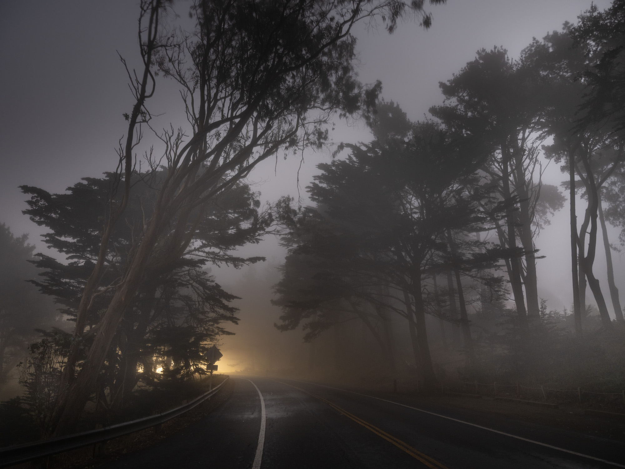 Road at night with fog and light in the distance.