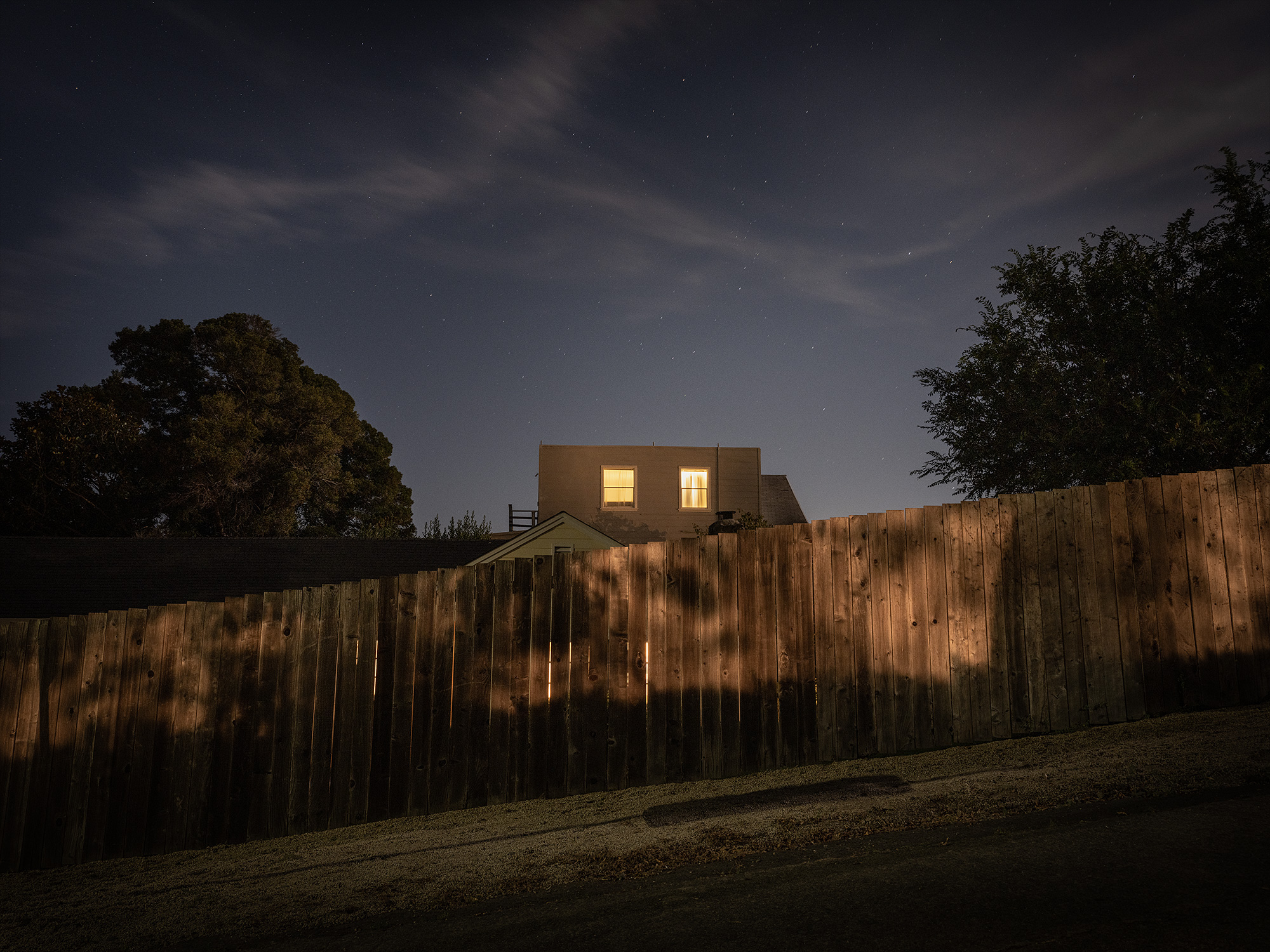 Home at night with fence with light behind it.