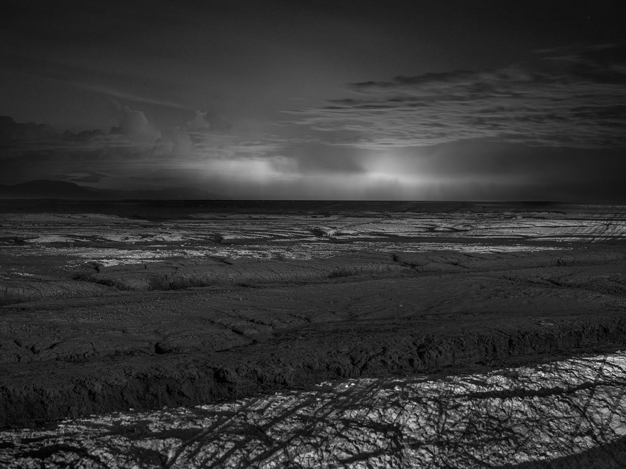 Black and white image of The Salton Sea at night with duststorm in background.