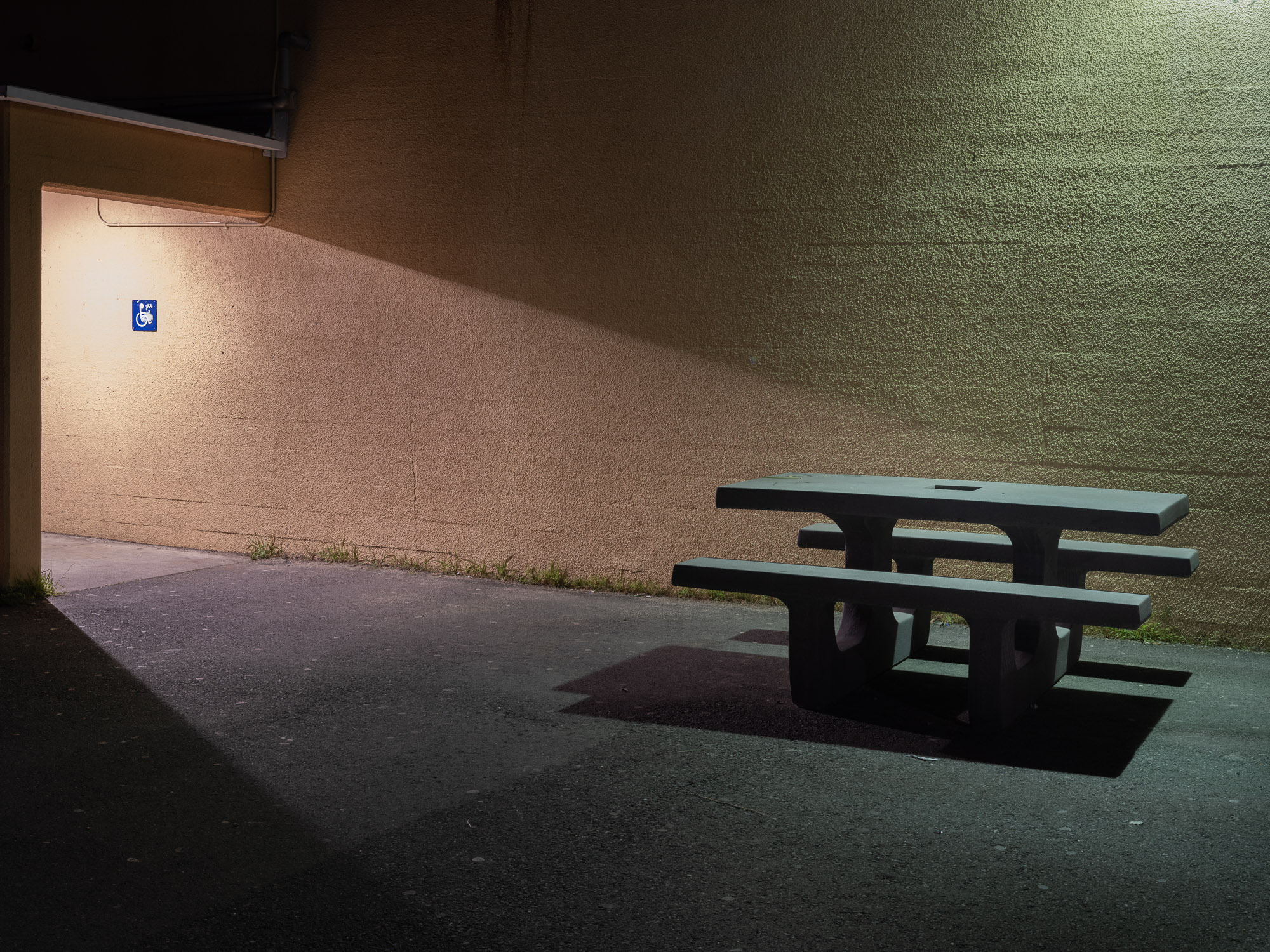 A concrete table at night with light hitting it from two directions.