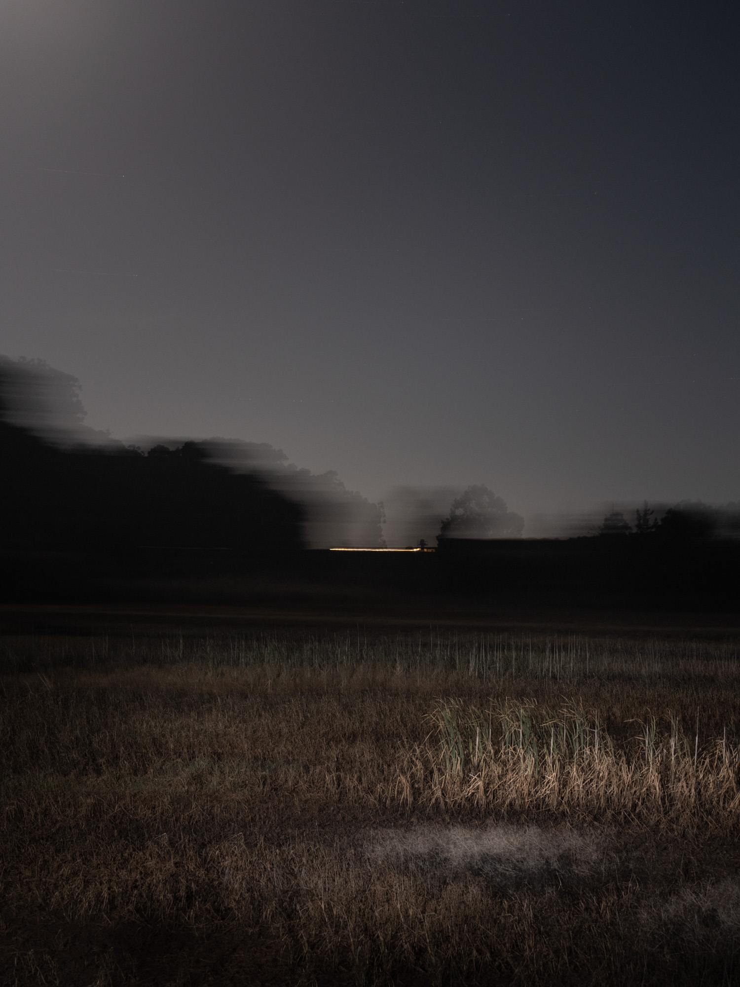 A landscape image of a field at night with light.