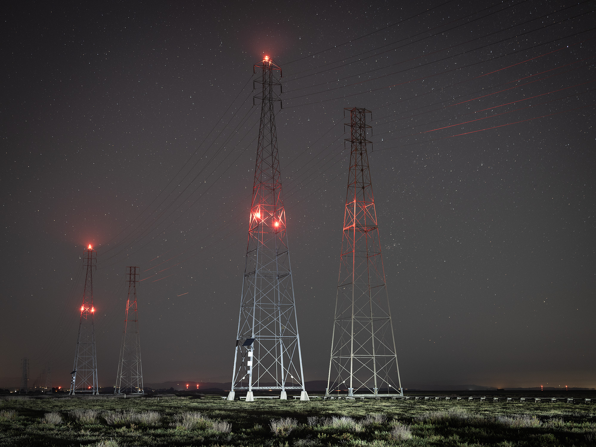 Image of power lines at night with stars in the background.