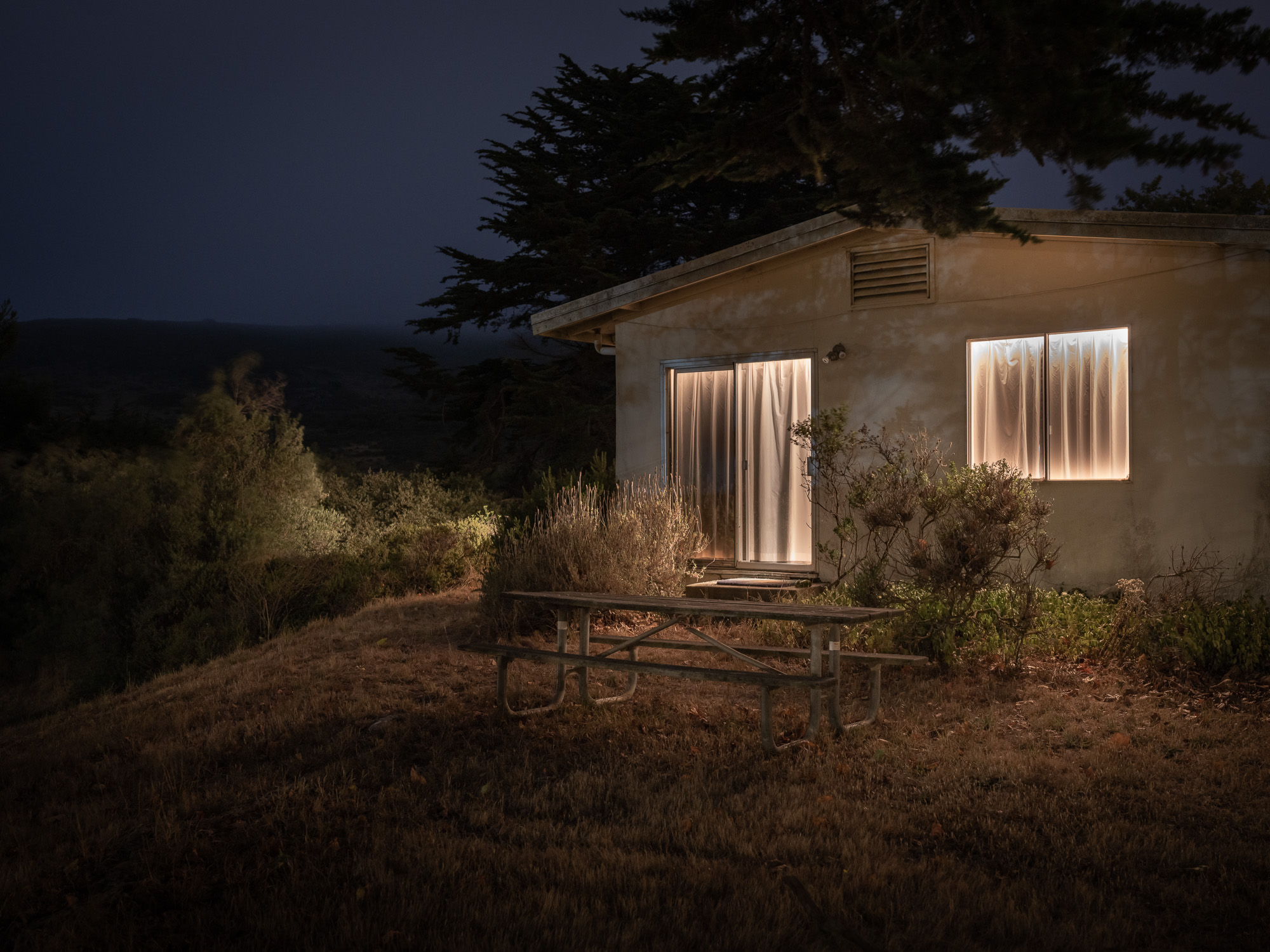 Image of house with curtains at night and table.