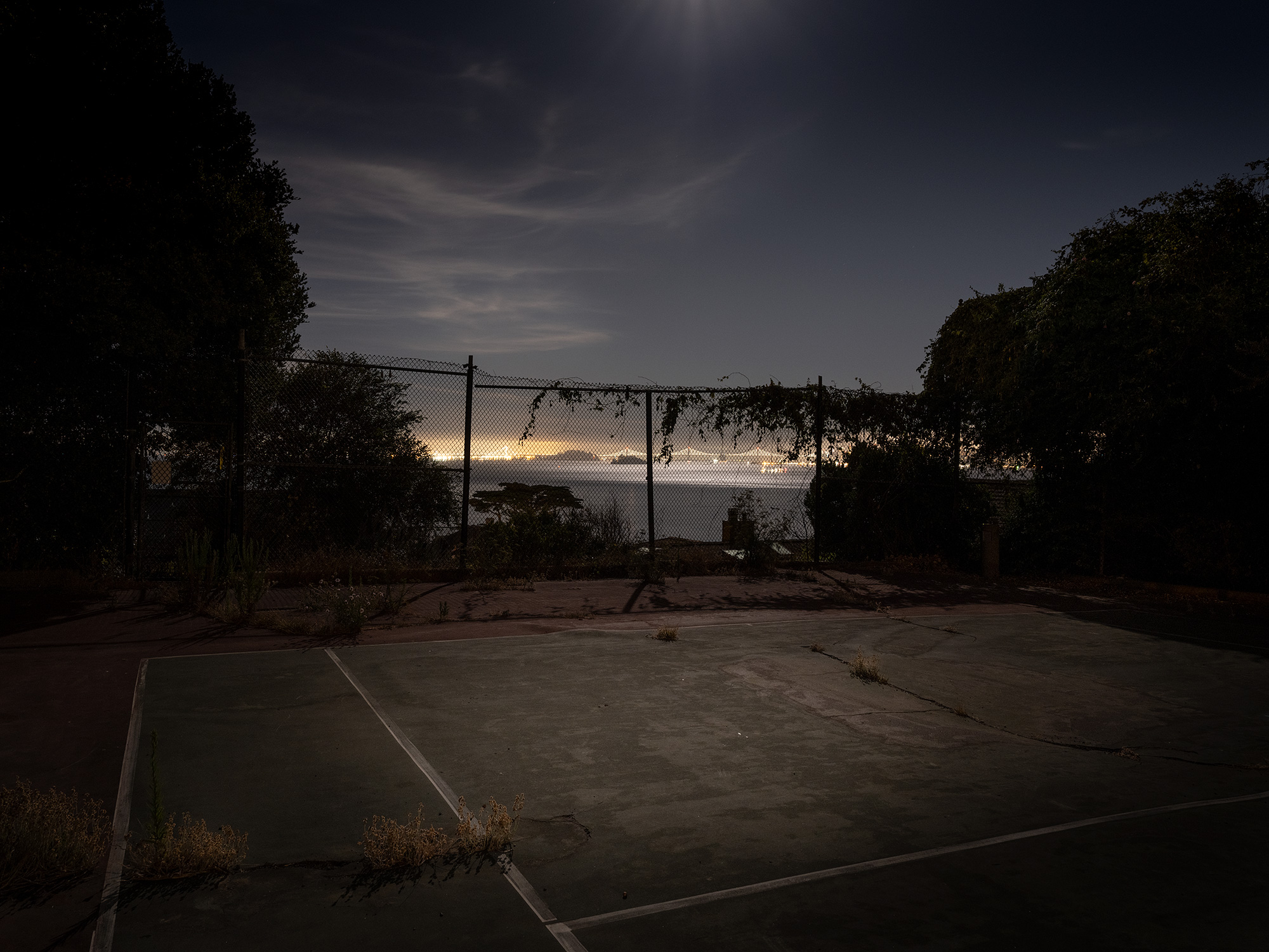 A tennis court at night overlooking The Bay Area.
